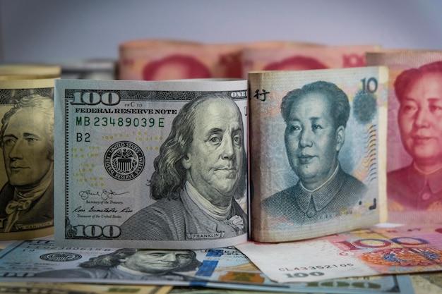 Van aangezicht tot aangezicht van dollar en yuan bankbiljetten die de vs en china oorlogshandel hebben en toenemen Premium Foto