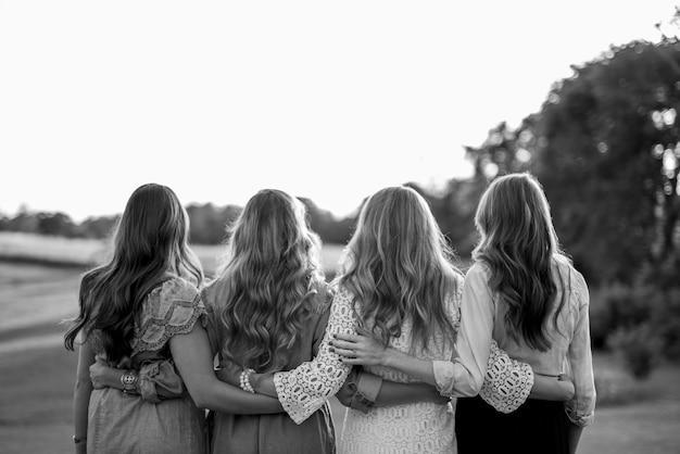 Van achteren neergeschoten van vier vrouwen met hun armen om elkaar heen in zwart-wit Gratis Foto