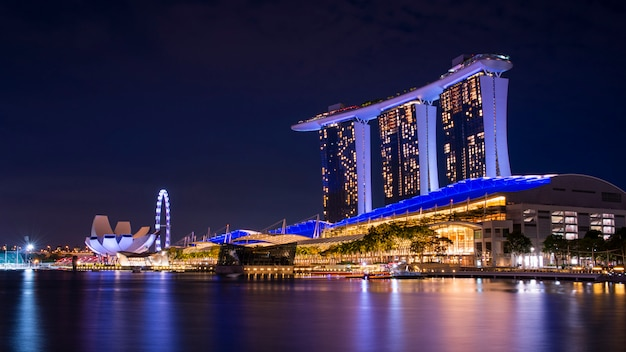 Van bedrijfs singapore de bouwhorizon bij dageraad met bezinning over waterbay in schemeringtijd. verlicht marina bay-zand bij nacht Premium Foto