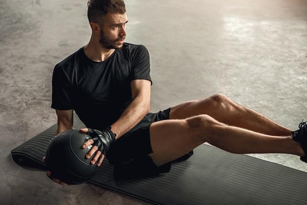 Van bovenaf bepaalde sportman abs oefening met bal op mat tijdens fitnesstraining in de sportschool doet Premium Foto