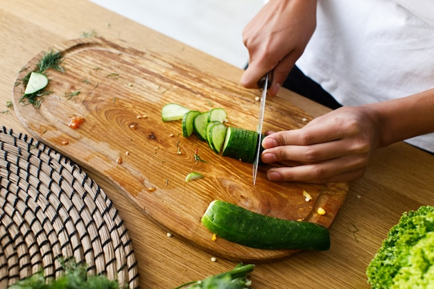 Van bovenaf snijdt de vrouw een komkommer op een keukenbureau Gratis Foto