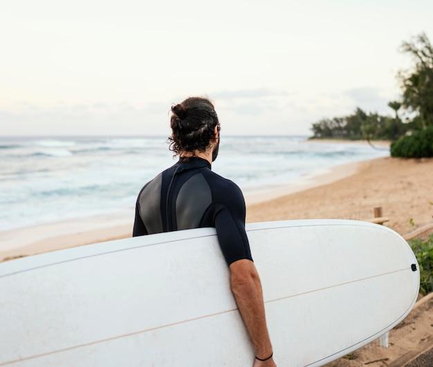 Van de achterkant schoot de surfer man buiten Gratis Foto