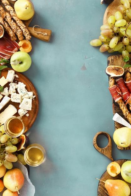 Van de de snacksfruit van de kaderwijn jamon kaas het kader hoogste mening als achtergrond Premium Foto
