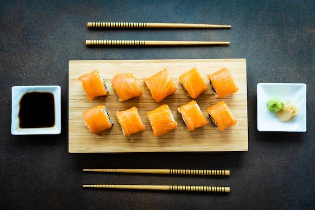 Van het vissensushi van zalmvissen het broodjesmaki op houten plaat Gratis Foto