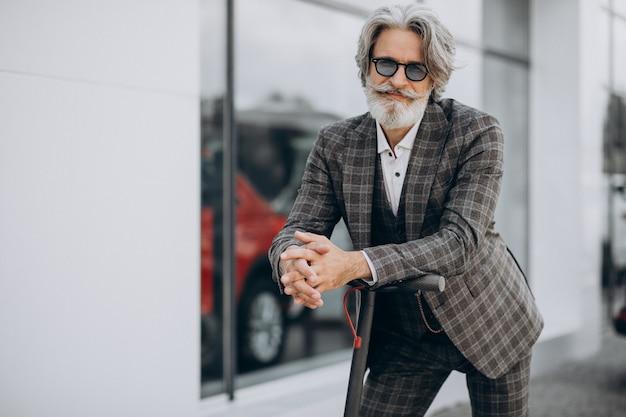 Van middelbare leeftijd zakenman rijden scooter in een stijlvol pak Gratis Foto