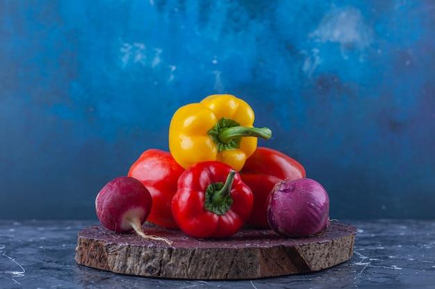 Variatie van verschillende kleuren paprika en radijs op stuk hout Gratis Foto