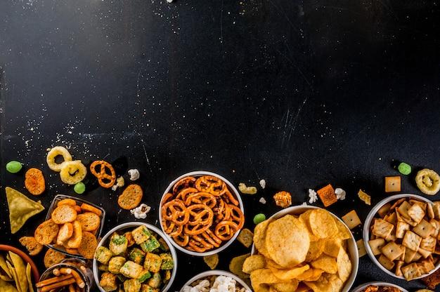 Variatie verschillende ongezonde snacks crackers, zoete gezouten popcorn, tortilla's, noten, rietjes, bretsels Premium Foto