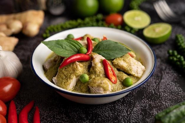 Varkensvlees groene curry in een witte kom met kruiden op een zwarte cement achtergrond Gratis Foto