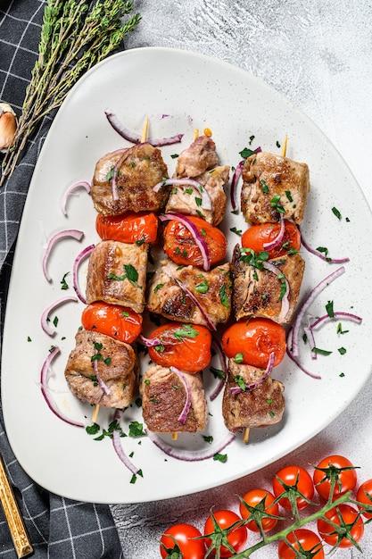 Varkensvlees kebab op spiesjes met tomaat en peper Premium Foto
