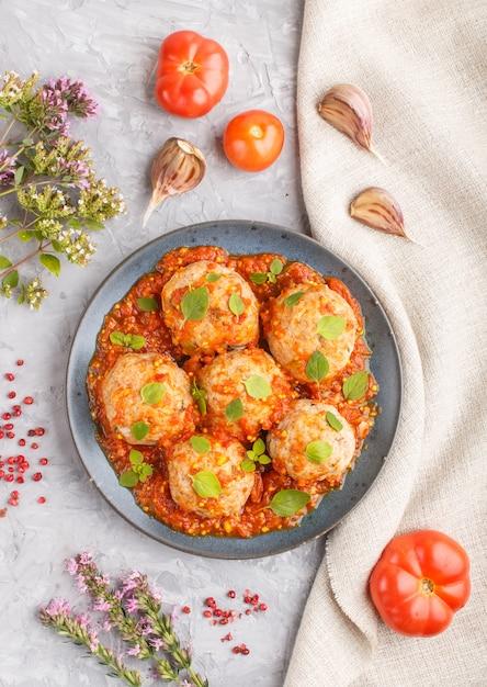 Varkensvleesballetjes met tomatensaus, oregobladeren, specerijen en kruiden op een grijze concrete achtergrond. bovenaanzicht Premium Foto