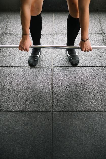 Vastberaden sportvrouw tillen van zware halter Premium Foto