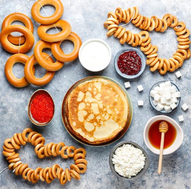 Vastenavond maslenitsa festivalmaaltijd. russische pannenkoekblini met frambozenjam, honing, verse room en rode kaviaar, suikerklontjes, kwark, bubliks op licht Gratis Foto