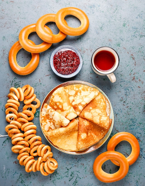 Vastenavond maslenitsa festivalmaaltijd. russische pannenkoekblini met frambozenjam, honing, verse room en rode kaviaar, suikerklontjes, kwark op donker Gratis Foto