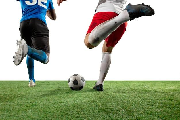 Vechten. close-up benen van professionele voetbal, voetballers vechten voor bal op veld geïsoleerd op een witte muur. concept van actie, beweging, hoog gespannen emotie tijdens spel. bijgesneden afbeelding. Gratis Foto