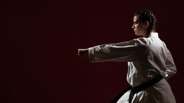 Vechtende vrouw in witte eenvormige karate en exemplaarruimte Gratis Foto