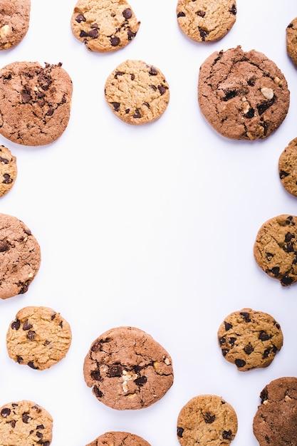 Veel chocolate chip cookies gerangschikt in een cirkel op een witte achtergrond met een kopie ruimte Gratis Foto