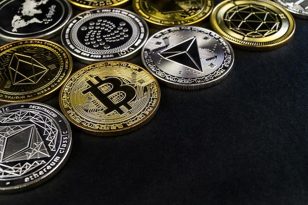 Veel cryptocurrency-munten liggen op een donkere ondergrond Premium Foto