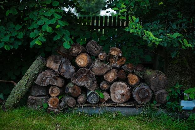 Veel hout en boomstammen in de achtertuin van een huis in dorp Gratis Foto