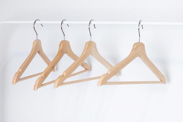 Veel houten hangers aan een staaf, geïsoleerd op een witte muur achtergrond. Premium Foto