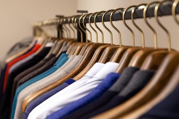 Veel houten hangers met verschillende mannelijke kleding in boetiek op metalen standaard. Premium Foto