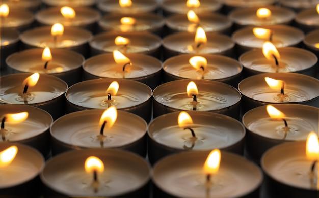 Veel kleine rondheid brandende kaarsen, close-up. Gratis Foto