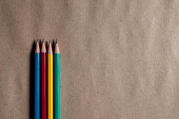 Veel kleurrijke potloden op bruin papier kunnen worden toegepast op ontwerpen. Premium Foto