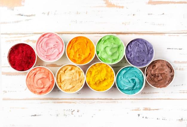 Veel kopjes met kleurrijk regenboog-ijs. bovenaanzicht Premium Foto