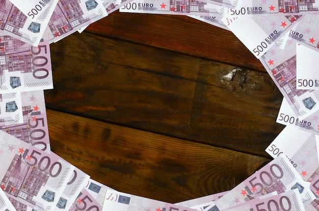 Veel paarse coupures ter waarde van 500 euro liggen op een houten oppervlak met een lege pad in het midden van het beeld. Premium Foto