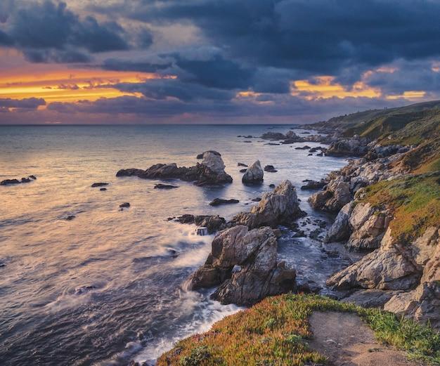 Veel rotsformaties bedekt met mos in de buurt van de zee onder de avondrood Gratis Foto