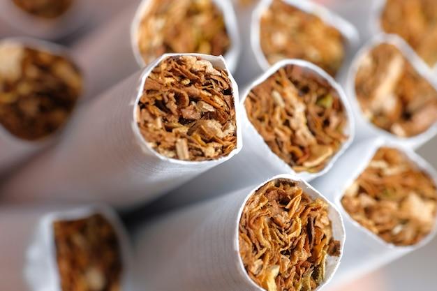 Veel sigaretten in wit papier. Premium Foto