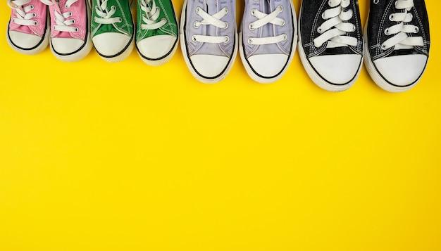 Veel textiel versleten sneakers van verschillende grootte op een gele achtergrond Premium Foto
