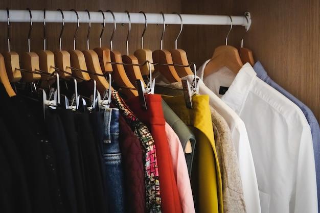 Veel verschillende kleren hangen in een kledingkast Gratis Foto