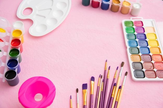 Veel verschillende penselen voor het tekenen met gouache en palet op een roze achtergrond. Premium Foto