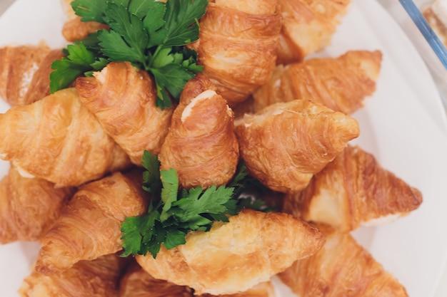 Veel verse croissants op een witte plaat op het buffet in het restaurant. Premium Foto
