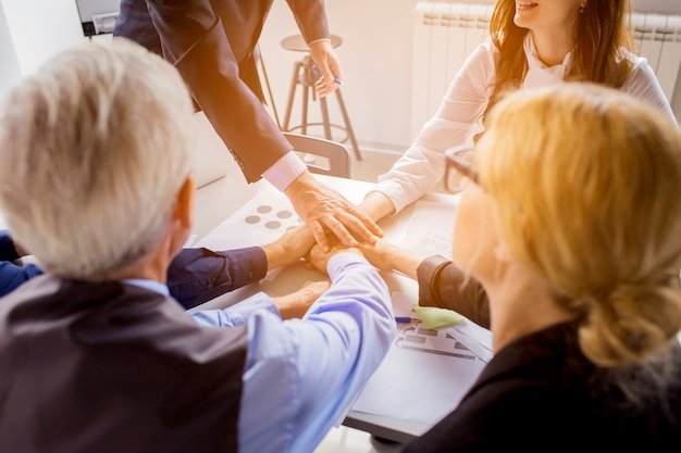Veel zakenlui bij handen samen op tafel in het kantoor Gratis Foto