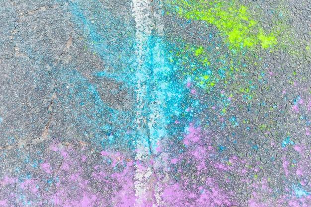 Veelkleurig holipoeder op asfalt Gratis Foto