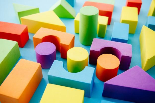 Veelkleurige geometrische vormen op een blauwe achtergrond. leren en Premium Foto