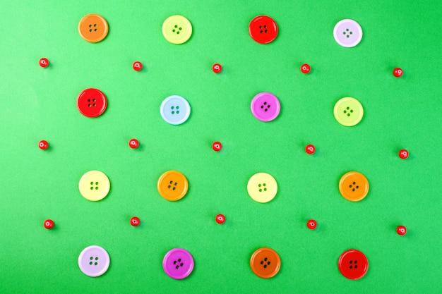 Veelkleurige knoppen en rode kralen op een groen oppervlak. Premium Foto