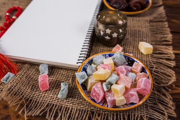 Veelkleurige kubussen van rakhat-lukum in plaat met lege witte spiraalvormige notitieboekje en kaarshouder op zaktafelkleed Gratis Foto
