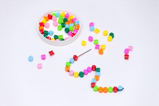 Veelkleurige kunststof kralen. zelfgemaakt spel voor kinderen ontwikkelingsconcept. Premium Foto