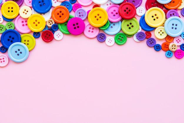 Veelkleurige naaien knoppen op een roze pastel oppervlak. rand naaien, bovenaanzicht Premium Foto