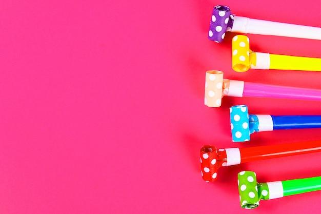 Veelkleurige partijventilators op roze achtergrond. veelkleurige feestfluitjes. decor voor een verjaardagsfeestje Premium Foto