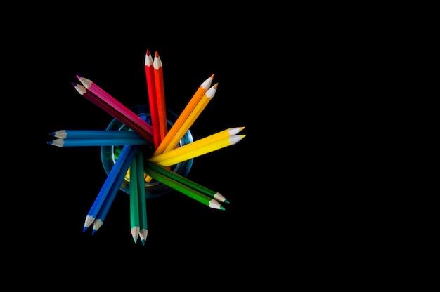 Veelkleurige potloden op een zwarte in de vorm van een hart, een plaats voor een inscriptie. Premium Foto