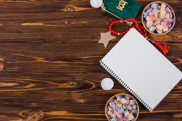 Veelkleurige rakhat-lukum kommen; kaars; kuran; rode parels en spiraalvormig lang notitieboekje op houten bureau Gratis Foto