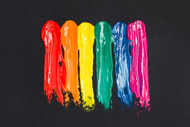 Veelkleurige strepen van olieverf op zwarte achtergrond Gratis Foto