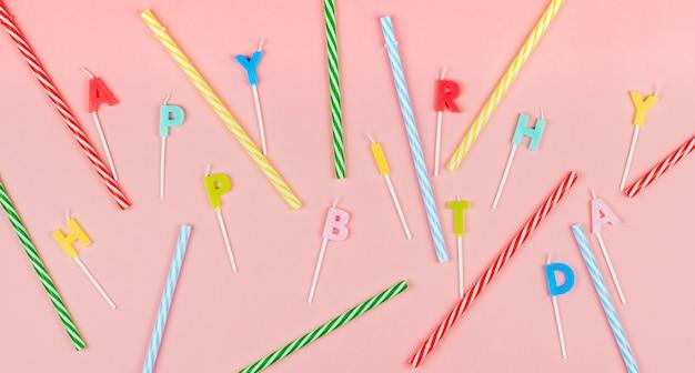Veelkleurige verjaardagskaarsen en gestreepte rietjes voor een cocktail Premium Foto