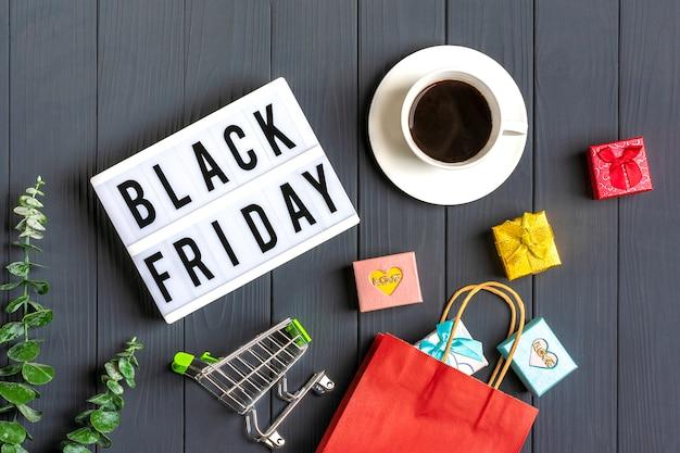 Veelkleurige verpakkingstassen, trolley, takje eucalyptus, kopje koffie geschenkdozen lightbox met tekst black friday op donkergrijs oppervlak Premium Foto