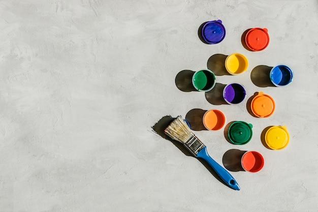 Veelkleurige verven in ronde potten en penseel op een grijs beton Premium Foto