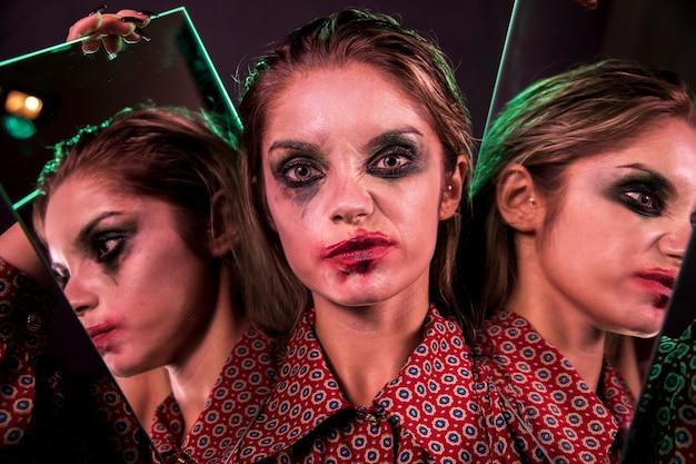 Veelvoudig spiegeleffect van vrouw die en camera smirking bekijkt Gratis Foto