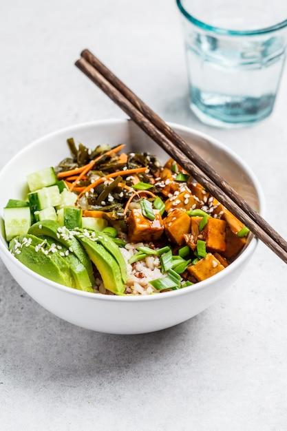 Vegan ahi poke bowl met tofu, rijst, zeewier, avocado en komkommer op wit Premium Foto